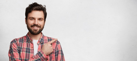 Horizontal portrait of cheerful attractive bearded male advertizes something, stands against white background with copy space for your promotional text. People, emotions, advertisment concept