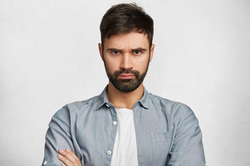 Portrait of serious displeased male stands crossed hands against white background, scowl face in dissatisfaction, has quarrel with wife. Discontent man has stubble, expresses annoyannce and negativity