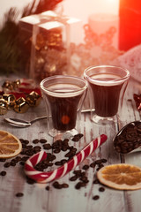 Black coffee in glass cups with christmas decoration and candies. Morning toned