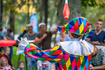 Back view streert juggler in bright clothing