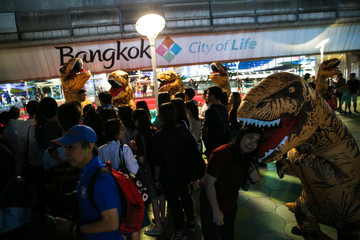 People pose for pictures with performers wearing T-Rex costumes at a shopping district in Bangkok