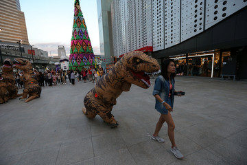 A performer wearing a T-Rex costume rides his skateboard toward a woman at a shopping district in Bangkok