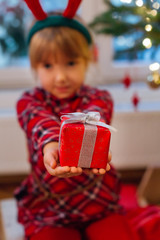 Girl sitting in her home holding Christmas presents