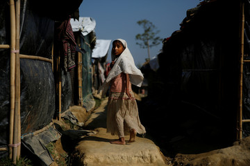 A Rohingya refugee girl makes her way at the Leda refugee camp near Cox's Bazar
