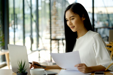 Cropped shot of a young businesswoman making notes while working on a laptop in a modern office.