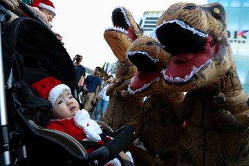 Performers wearing T-Rex costumes play with infants wearing Santa Claus costumes, at a shopping district in Bangkok
