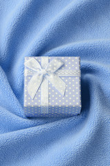 A small gift box in blue with a small bow lies on a blanket of soft and furry light blue fleece fabric with a lot of relief folds. Packing for a gift to your lovely girlfriend