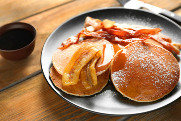 Tasty pancakes with bacon and banana on table