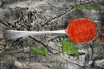 Spoon with delicious red caviar on textured background, top view