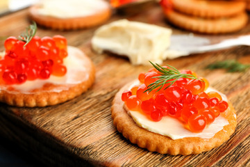 Cracker with butter and red caviar on wooden board, closeup