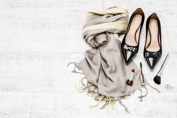 Black shoes, luxurious scarf and cosmetics.