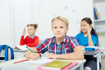 Serious schoolboy with pencil looking at camera by desk while drawing at lesson