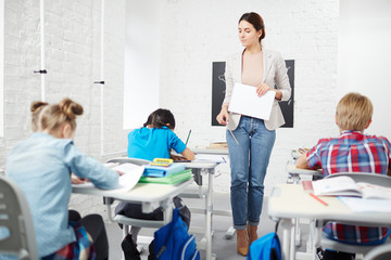 Strict teacher walking down between desks while schoolkids carrying out individual task