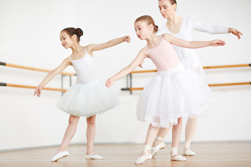 Two little girls leaning aside while repeating after their teacher during training