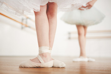 Legs of little girl wearing satin points and shiffon skirt during ballet lesson