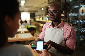 Modern customer holding her smartphone over payment terminal held by waiter