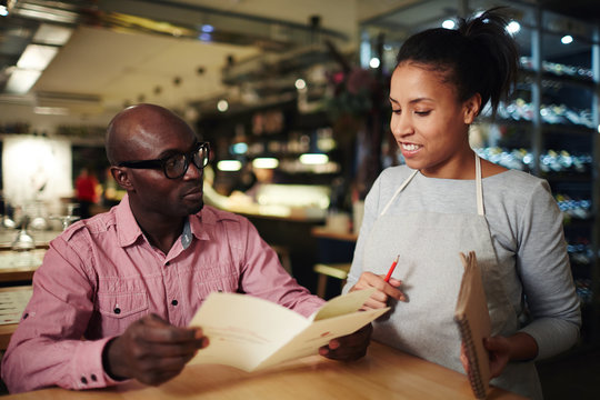 Young man with menu choosing food and listening to waitress recommendations in restaurant