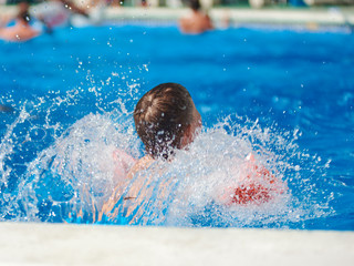 Caucasian boy swimming in the pool.