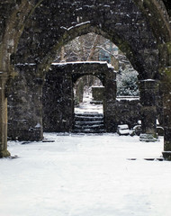 ruined church in snowfall with doorway and arches in heptonstall west yorkshire