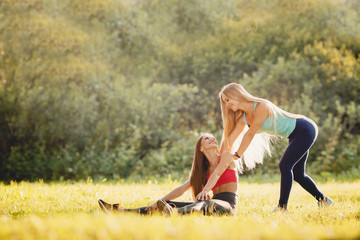 Fitness. Girls group of friends train in park with yoga and fitness