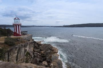 Kleiner Leuchtturm auf Fels-Klippe im Hafenbecken von Sydney in Australien