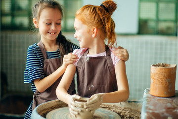 pottery workshop - two girls sculpts from clay on pottery wheel