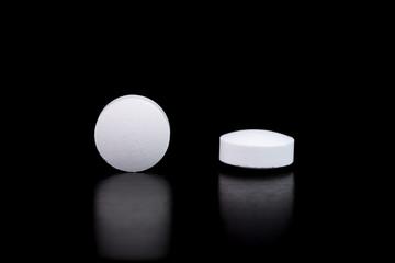 White pharmaceutical pills on black background