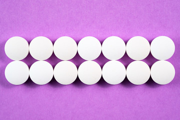 White round pharmaceutical pills on colorful background