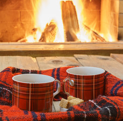 Two cups  of  tea, woolen things near cozy fireplace, in country house, winter vacation, horizontal.