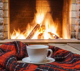 Cup  of  tea, woolen things near cozy fireplace, in country house, winter vacation, horizontal.