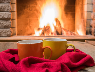 Two mugs  of  tea, woolen things near cozy fireplace, in country house, winter vacation, horizontal.