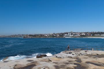 Einsame Frau auf einem felsigen Aussichtspunkt mit Blick aufs offene Meer