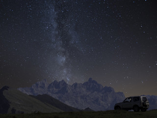 4x4 offroad Car under mountains and milky way at night, adventure concept