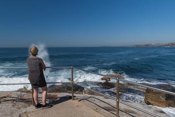 Frau steht am Aussichtspunkt und betrachtet die Brandung und das Wellenspiel im Meer