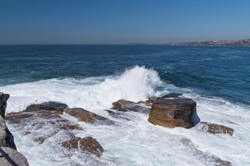 Spritzende Brandung schlägt gegen Felsbrocken in der Bucht
