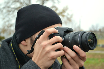 A guy with a camera in the autumn on the street