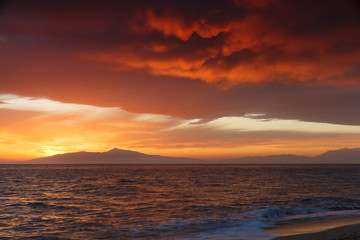 Crimson sunset on the shore of the orange sky and calm sea witt view at the mountains