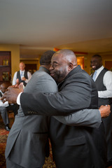 Father and hugging her adult son at his wedding.