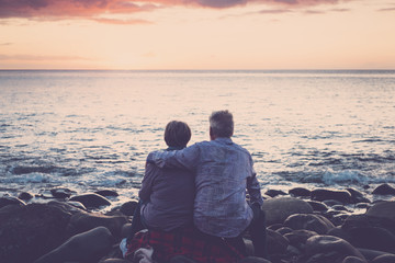 gentlemen couple sitting at the beach at sunset. hug and love view from back rear. foreverness concept. people on vacation and ocean in background