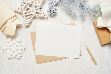 Mockup Christmas greeting card letter in envelope with white tree, flatlay on a white wooden background, with place for your text, Flat lay, top view photo mock up