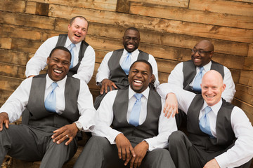 Groom and groomsmen smiling at a wedding.