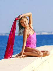 Young beautiful girl in a joint pink swimsuit is sitting on a pier by the sea.