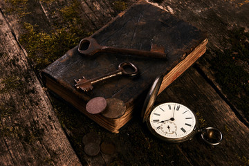Antique pocket watch, old book with ancient copper coins