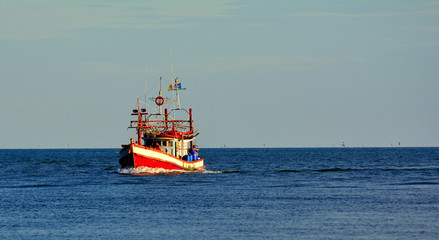 One fisherman boat in a sea blue sky background