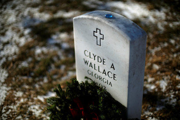 A Christmas wreath and glass pebble rest on a headstone at Arlington National Cemetery in Arlington
