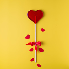 Valentine's day bright yellow background, greeting card concept,  lollipop or sweet candy on sticks, with gift box, note and decorative hearts.