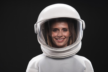 Feeling happiness. Portrait of charming delighted female astronaut wearing helmet and protective suit is standing and looking at camera with wide smile. Isolated background