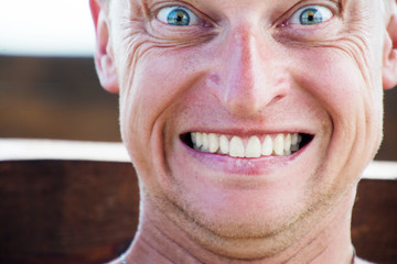 Close up portrait of funny man, grins his teeth