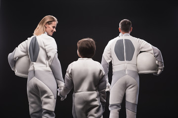 Harmonious relations. Back view of positive astronaut mother is holding by hand her little son while standing together with father. Isolated background. Migration concept