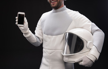 Useful device. Delighted bearded cosmonaut wearing hyperbaric protective costume is standing and holding helmet and mobile phone. He is showing screen of gadget to camera. Isolated background